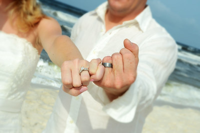 Photo of a couple showing their rings with interlocking fingers