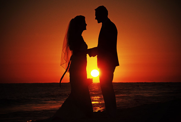 Newlyweds holding hands in front of the Sunset